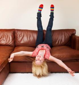 84743298-teenage-girl-upside-down-on-sofa-gettyimages