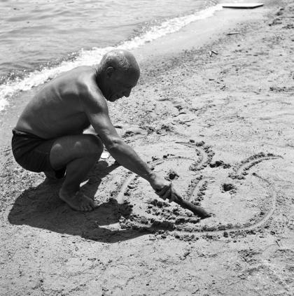 Pablo Picasso dessinant sur le sable Juan-les-pins (1953)