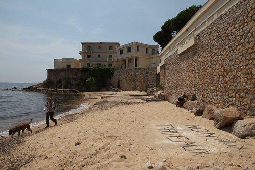 """La famille royale saoudienne ordonne des travaux sur une plage publique de Golfe-Juan Des ouvriers ont coulé une dalle de béton sur la plage publique de La Mirandole, sous la villa du roi Fahd. Le maire, Michelle Salucki, a alerté les services de la sous-préfecture de Grasse """"Ça s'est passé vendredi entre midi et deux. Des ouvriers ont coulé une dalle en béton à même le sable ! Ils ont installé des barrières autour. Et les travaux continuent. La poussière et le bruit nous empêchent de profiter de ce lieu idyllique. Des ouvriers ont même dit à une dame d'en profiter, Car bientôt il n'y aurait plus d'accès possible!"""" Daniel Guilleminot, un résident du quartier Cannes-Eden, à Golfe-Juan, n'en revient pas. Il pointe un doigt accusateur au-dessus de la dalle de trois mètres sur quatre, en direction de la résidence qui appartient au roi Fahd. Une ouverture a été faite, dans le béton de la terrasse qui surplombe le site. La compétence de l'État De là à déduire que les ouvr"""