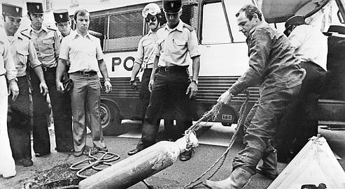 Un policier retire une bouteille à oxygène des égouts de Nice le 20 juillet 1976. AFP PHOTO